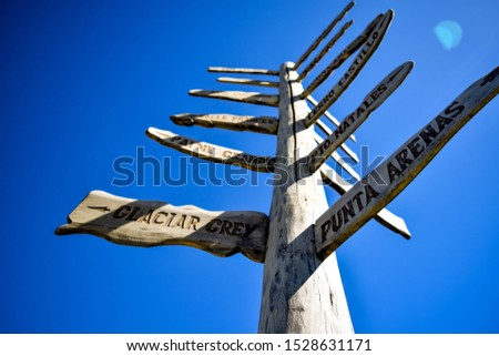 arrow sign with many directions on a blue background, torres del paine #1528631171