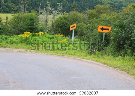Arrow signs pointing both ways on a steep curve in New Brunswick, Canada
