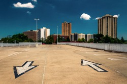 Arrows in parking lot and view of highrises from a parking garage in Towson, Maryland.