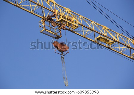 Arrows of construction cranes against the blue sky and buildings under construction #609855998