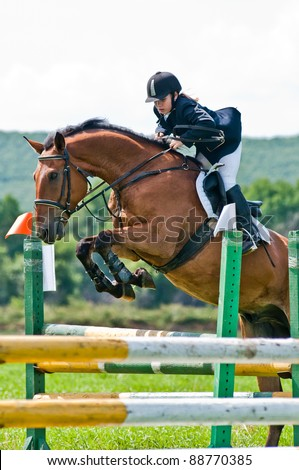 "ARSENEV, RUSSIA - SEPTEMBER 03: Unidentified child-rider in action jumps over a hurdle at horse on the show jumps ""Cup of Governor of the Primorsky Territory, 2011"" on Sept 03, 2011 in Arsenev, Russia"