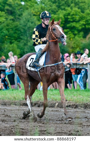 """ARSENEV, RUSSIA - SEPTEMBER 03:  Unidentified jockey after finish line in the mud on Riding show """"Cup of the Governor of Primorsky Territory, 2011"""" on Sept 03, 2011 in Arsenev, Russia - stock photo"""