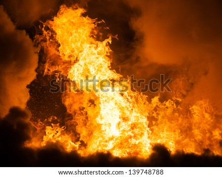 Arson or nature disaster - burning fire flame on wooden house roof stock photo