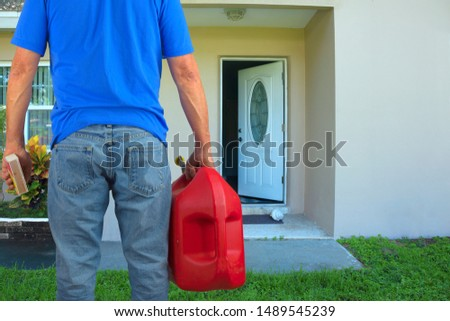 Arsonist man with red plastic gasoline can container and box of striking matches preparing to commit arson crime and maliciously and  intentionally burn down a house with an open front door. Stock photo ©