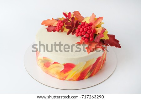 Art cake with whipped yellow, orange and green cream, decorated with autumn leaves from mastic. Picture for a menu or a confectionery catalog.
