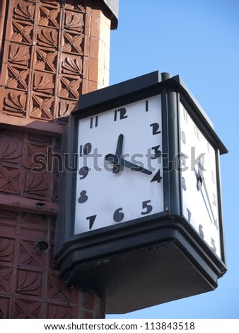Art Deco clock on the side of an ornate building in Detroit Michigan.