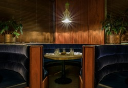 Art deco style velvet booth seat and table set in a room with wood paneling on the walls and vintage light fixture, with light burst effect