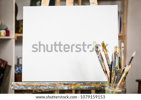 Art equipment: easel, brushes, tubes with paint, palette and paintings.