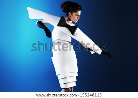 Art fashion photo of a gorgeous woman in paper dress over blue background. Black and white. #155248115