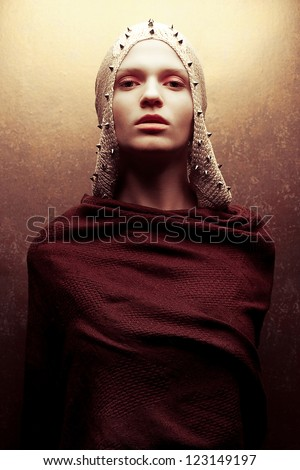 Art-fashion portrait of a glamorous queen-warrior in golden cape with golden pricks. Studio shot