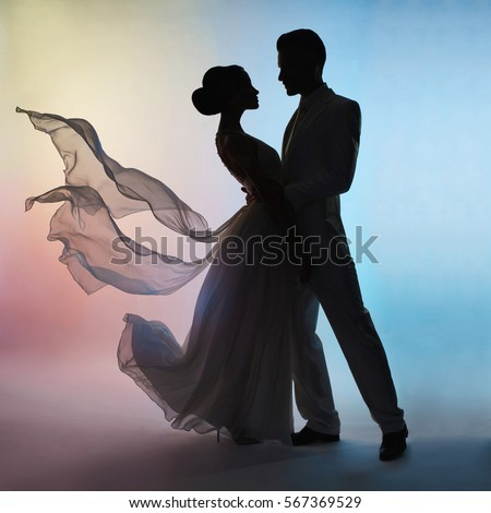 Art fashion studio photo of wedding couple silhouette groom and bride on colors background. Art Wedding style. Flowing dress. Dance of groom and bride