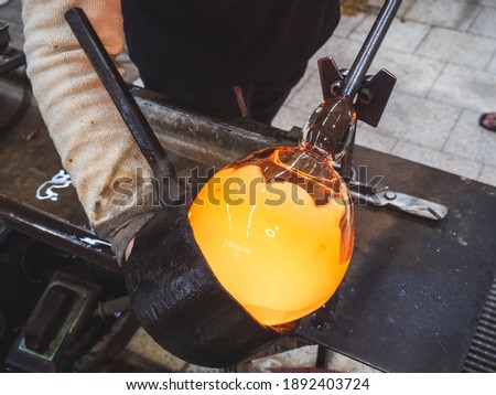 Photo of  Art glassblower use wet wooden form for shaping the red melted glass on the end of glassblowing pipe. Traditional handmade Czech glass workshop in Kunratice.