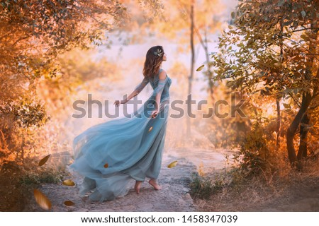 art goddess girl. blue vintage evening clothing. dress long fly fluttering silk train, Beauty woman princess wind storm, young lady brunette hair back fallen golden leaves backdrop autumn forest park