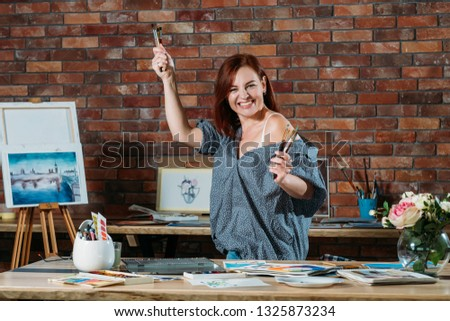 Art hobby. Studio workspace atmosphere. Enthusiastic redhead female posing with paintbrushes and easel in background.