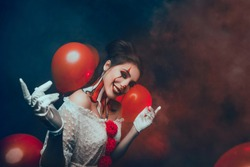 Art Holiday event party. Adult happy comedy Lady Clown smiling Invite Performance. Artistic creative vintage circus white costume. Red scary makeup hairstyle brunette dark hair bagels bun. Young face