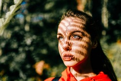Art lifestyle creative closeup portrait of  odd young pretty long haired girl at nature outdoor. Charming teen with beautiful shadow pattern from sunlight falling on her face through fern branch