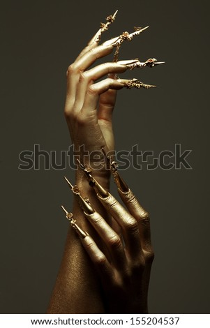 Art Manicure Concept. Beautiful golden hands with golden long arty nails. Close up. Studio shot