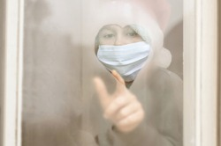 Art noise. Child in a santa claus hat, protective mask draws a heart on the foggy misted window with his finger. Christmas holidays 2021. Covid-19, Coronavirus. Waiting. Isolation at home. Hospital
