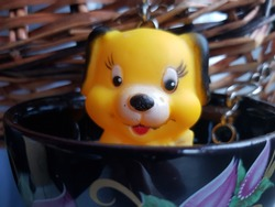Art of Abstraction in the Photo: funny joyful toy puppy looks out of a decorative glass bowl on the background of a wicker basket in the room