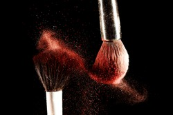 Art of visage.  Horizontal closeup photo of two professional black make-up brushes with red powder isolated on black background with copy place