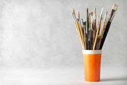 Art paint brushes in cup with empty room for text