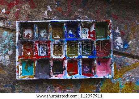 art palette with blobs of paint on wooden background