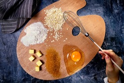 Art palette with food ingredients for oat cookies and with a woman hand with brush-whisk for whipping, top view, dark stone table
