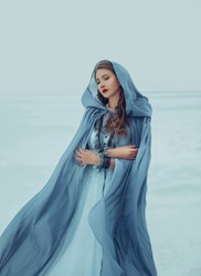 Art photo. Fantasy young woman fairy elf in blue cape with hood stands in cold wind. Winter nature background, white snow. Girl Queen walks in medieval dress, silk cloak, fabric is waving, fluttering.