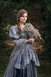 Art photo of a fairy-tale girl with a braid and an owl in her arms