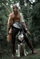 Art photo of a girl hunter with bow and husky on a background of dark forest