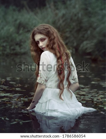Art photo of a gloomy mystical girl in swamp water