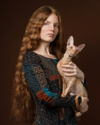 Art photo of a red-haired woman in an ethnic dress with a red Cornish Rex cat in her arms