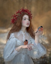 Art photo of a tender red-haired girl with two little red bullfinches