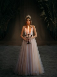 Art photo of medieval girl princess walks in dark gothic room. Woman queen is holding candlestick with burning candles in hand. Pink purple dress, long loose blonde hair, gold royal crown. Fairy image