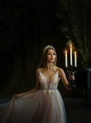 Art photo of medieval girl princess walks in dark gothic room. Woman queen is holding candlestick with burning candles in hand. Pink purple dress, long loose blonde hair, gold royal crown.