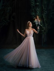 Art photo of medieval girl princess walks runs in dark gothic room. Woman queen is holding candlestick with burning candles in hand. Pink purple dress fly in motion. long blonde hair, gold royal crown
