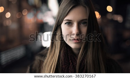 Art portrait of a beautiful girl. gorgeous brunette girl, portrait in night city lights. Vogue fashion style portrait of young pretty beautiful woman with long dark curly hair.