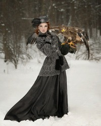 Art portrait of a red-haired girl dressed as an aristocrat with a steppe eagle on her arm