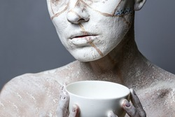 Art portrait of woman covered in clay isolated over grey background. Woman face like cracked earth holding  a cup