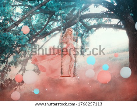 Photo of  Art princess elf stands swinging on magical forest swing mystical tree. Woman nymph in long pink dress skirt fluttering fly wind. Fantasy nature white blue balls, air balloons. red fog colorful smoke