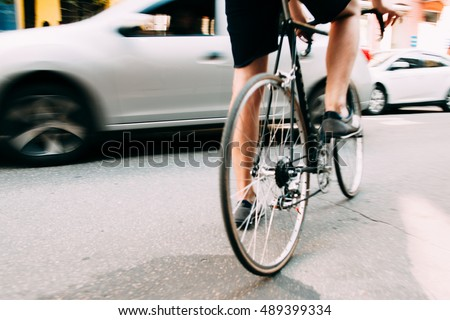 Art street photography. Man start riding on bicycle in city. Close-up of male legs on bike in street near gray car, blurry photo. Healthy lifestyle concept
