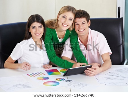 Art students with tablet computer learning color theory in the university