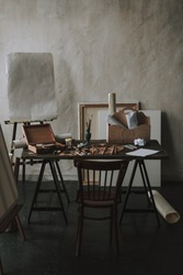 Art studio with table and painting equipment on it. Drawing easel on the background