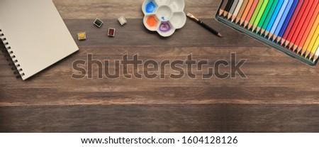 art supplies (sketchbook, watercolors, pencils) on rustic wood surface