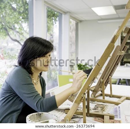 Art teacher paints in preparation for class