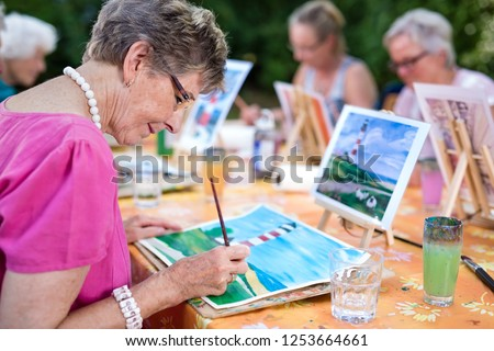 Art therapy for senior ladies, group of women painting the picture of lighthouse from the watercolor template  sitting at one table outdoors in the park.