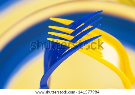 Art, Two plastic forks, blue and yellow, put together in a gesture of prayer