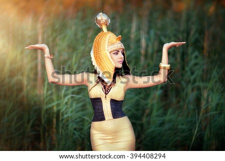 Art work Egyptian Queen Cleopatra. Shooting outdoors in the style of ancient Egypt. A beautiful young girl in gold dress and Egyptian head wear raising hands in sun light. Egyptian make up face.