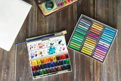 art workplace, pencils, brushes, watercolor paints, paper and crayon pastel chalks. Flat lay.wooden table