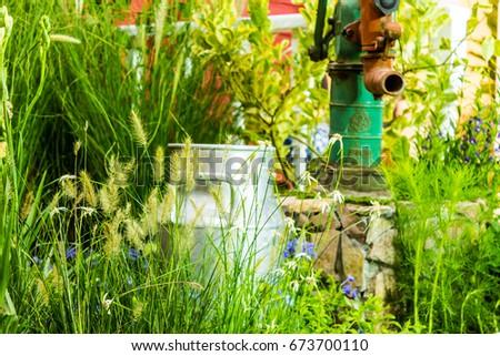 Artesian well and bucket in cozy garden on summer./ Artesian well and bucket.